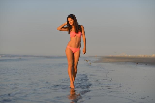 水着を着て波打ち際を歩く外国人女性4