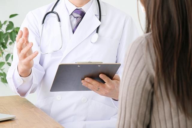 カルテを見ながら問診する医師