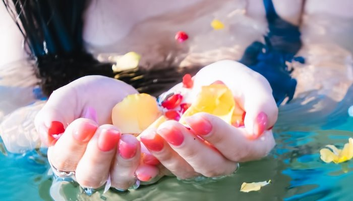 水面に浮く鮮やかな花びらと女性の手