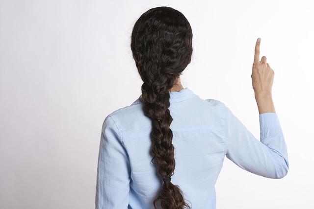 人差し指を立てる後ろ向きの女性